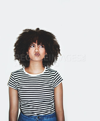 Buy stock photo Studio shot of a young woman pulling faces against a gray background