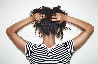 Buy stock photo Rearview studio shot of a woman lifting the hair off of her neck against a gray background