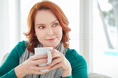 Buy stock photo Cropped shot of a mature woman drinking coffee while relaxing on the sofa at home