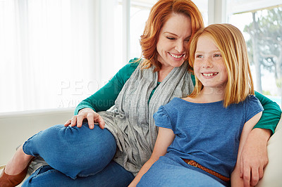 Buy stock photo Shot of a mother and young daughter sitting on the sofa at home