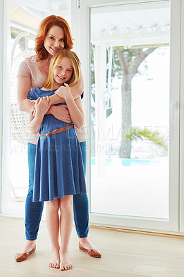Buy stock photo Full length portrait of a mature woman hugging her young daughter at home