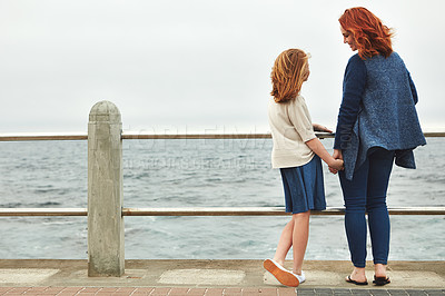 Buy stock photo Rearview shot of a woman and her young daughter at the waterfront