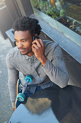 Buy stock photo Shot of a young skater talking on his phone at a sidewalk cafe