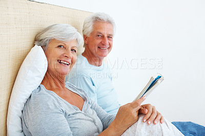 Buy stock photo Portrait of senior couple sitting on bed and smiling with woman reading a book