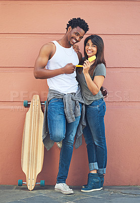 Buy stock photo Shot of a happy young couple eating ice lollies together