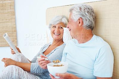 Buy stock photo Senior couple sitting on bed and smiling with woman reading a book and man eating breakfast