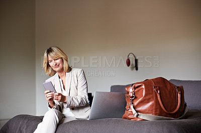 Buy stock photo Shot of a mature businesswoman sitting on a hotel bed using her cellphone