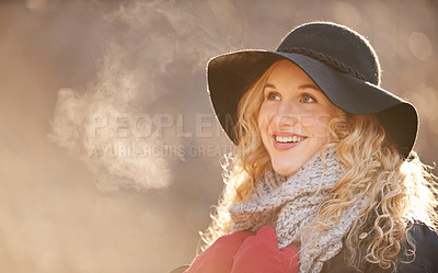 Buy stock photo Shot of a young woman looking at her breath while on a walk outdoors in winter