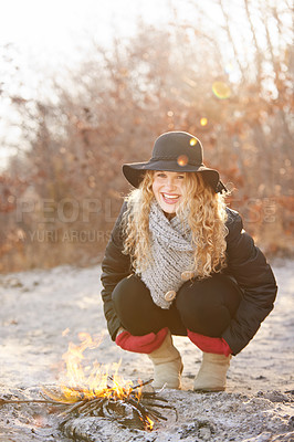 Buy stock photo Shot of a young woman trying to stay warm by a fire outdoors