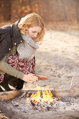 Buy stock photo Shot of a young woman trying to stay warm by a fire outdoors in winter