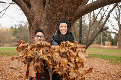Buy stock photo Shot of a happy young couple playing with leaves on an autumn day in the park
