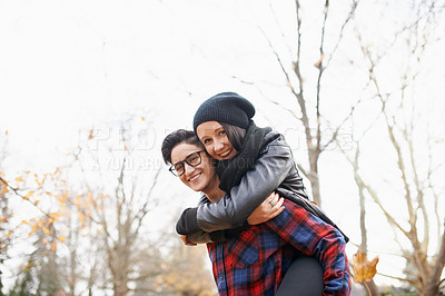 Buy stock photo Shot of a happy young couple enjoying a piggyback ride in the park on an autumn day