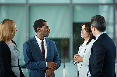 Buy stock photo Shot of a diverse group of businesspeople talking together in the lobby of an office building