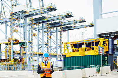 Buy stock photo Shot of a man in workwear standing outside on a large commercial dock using a digital tablet
