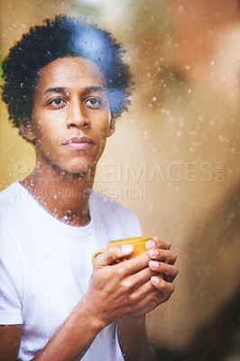 Buy stock photo Shot of a thoughtful young man drinking coffee while looking out of the window on a rainy day