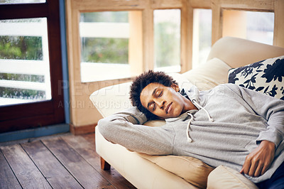 Buy stock photo Shot of a young man having a nap on the sofa at home