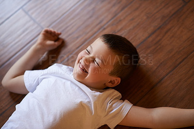 Buy stock photo Shot of a happy little boy playing on the floor