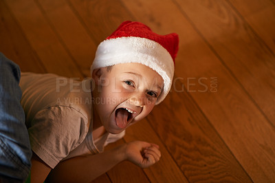 Buy stock photo Shot of a playful little boy wearing a santa hat at home during Christmas