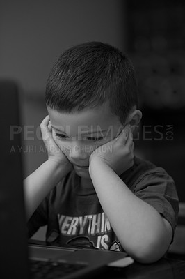 Buy stock photo Black and white shot of a little boy staring at a laptop screen at home