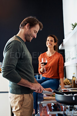 Buy stock photo Shot of a smiling mature couple cooking dinner together in the kitchen