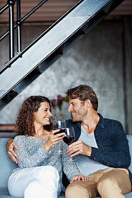 Buy stock photo Shot of a mature couple drinking wine while sitting on a sofa in their living room