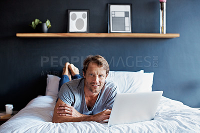 Buy stock photo Portrait of a mature man lying on his bed using a laptop
