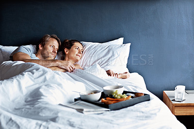 Buy stock photo Shot of a mature couple relaxing in bed with breakfast