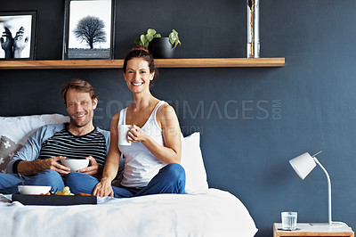 Buy stock photo Portrait of a smiling mature couple enjoying breakfast in bed