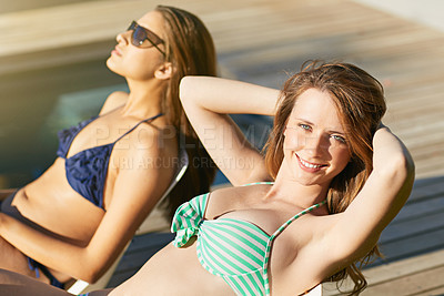 Buy stock photo Portrait of a young woman and her friend suntanning by a swimming pool