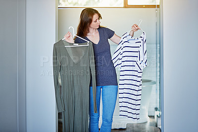 Buy stock photo Shot of a young woman standing in her bathroom choosing outfits