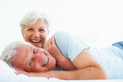 Buy stock photo Closeup portrait of senior couple lying in bed and smiling
