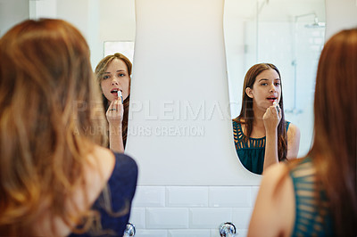 Buy stock photo Rearview shot of two young friends putting on makeup in the bathroom mirror