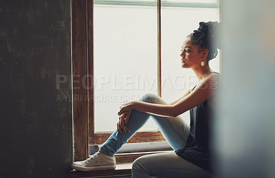 Buy stock photo Shot of an attractive young woman sitting by the window