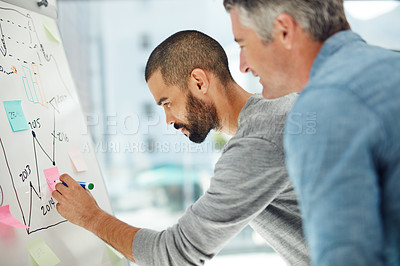 Buy stock photo Cropped shot of two businessmen working at a whiteboard
