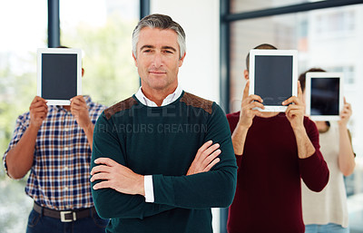Buy stock photo Cropped portrait of a mature businessman standing with his colleagues who are covering their faces with tablets