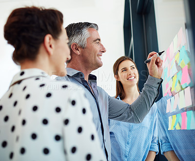 Buy stock photo Cropped shot of three businesspeople working at a whiteboard