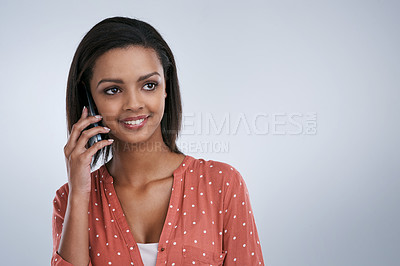 Buy stock photo Studio shot of a young woman speaking on a cellphone against a grey background