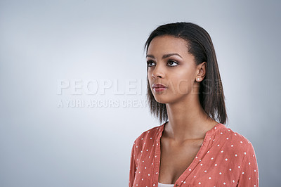 Buy stock photo Studio shot of a young woman looking thoughtful against a grey background