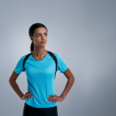 Buy stock photo Studio shot of a sporty young woman looking thoughtful against a gray background