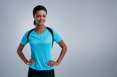 Buy stock photo Studio portrait of a sporty young woman posing confidently against a gray background