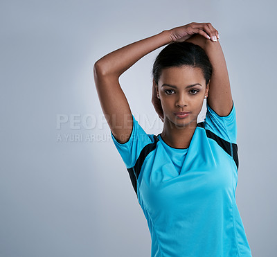 Buy stock photo Studio shot of a sporty young woman stretching against a gray background