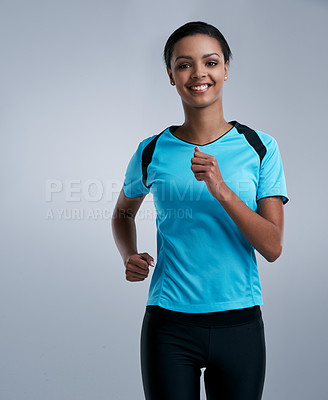 Buy stock photo Studio portrait of a fit young woman running against a gray background