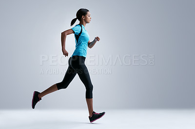 Buy stock photo Studio shot of a fit young woman running against a gray background