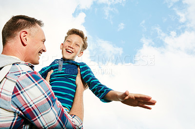 Buy stock photo Shot of a dad standing outside holding his son up in the air