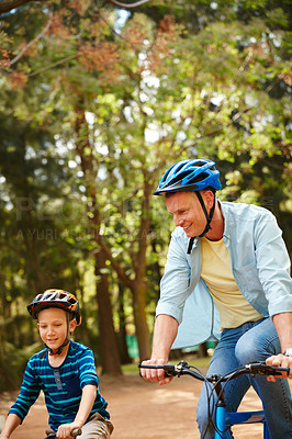 Buy stock photo Shot of a father and his young son riding bicycles through a park