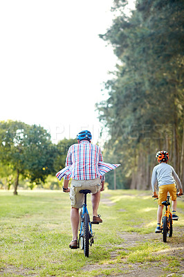 Buy stock photo Rearview shot of a father and son riding bicycles in a park