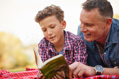 Buy stock photo Shot of a father and son reading a book together in a park