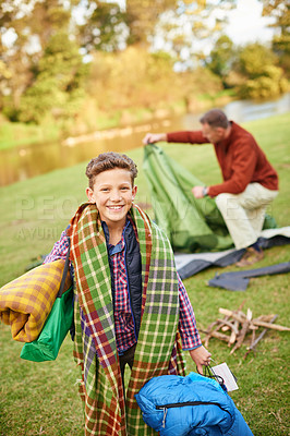 Buy stock photo Portrait of a young boy holding camping gear with his father in the background