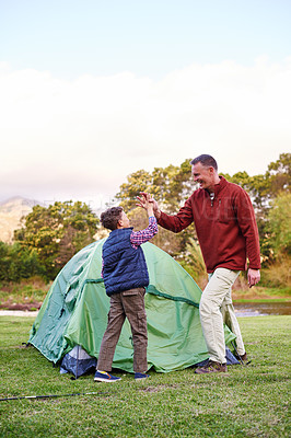 Buy stock photo Shot of a father and son hi fiving after setting up a tent together while camping