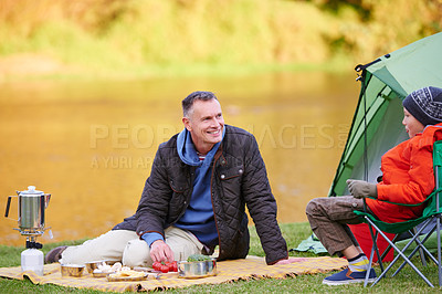 Buy stock photo Shot of a father and son preparing a meal while camping
